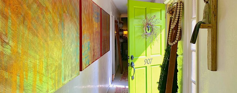 A gallery wall of foil artwork and a chartreuse door in a hallway.